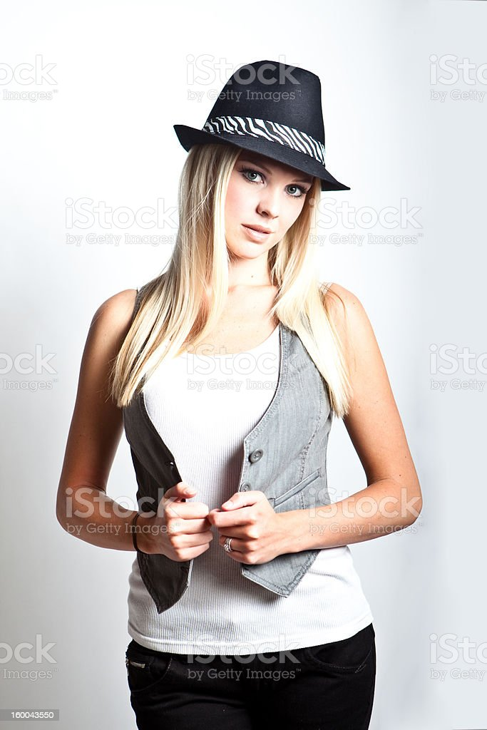 Pretty girl holding onto her vest wearing a hat royalty-free stock photo