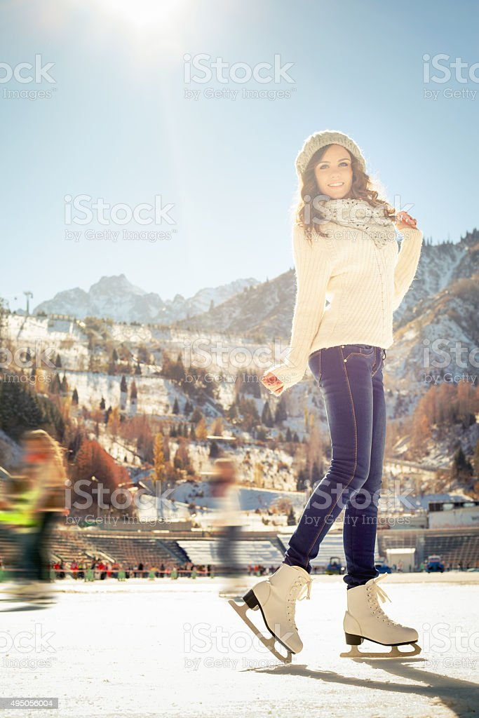 Pretty girl ice skating outdoor at ice rink stock photo