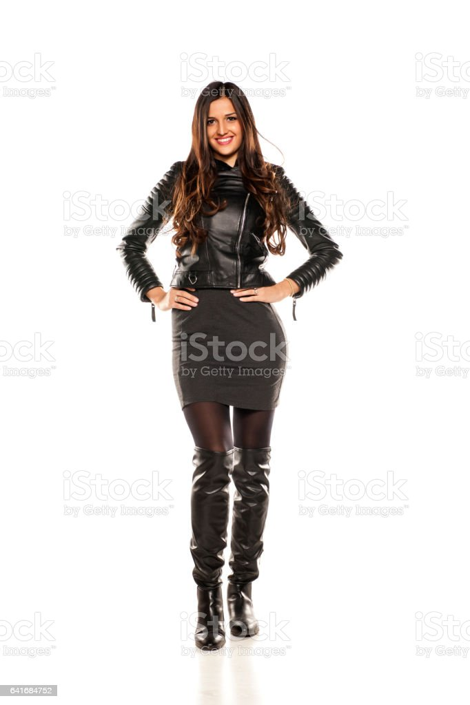 pretty girl in a leather jacket and boots on white background stock photo