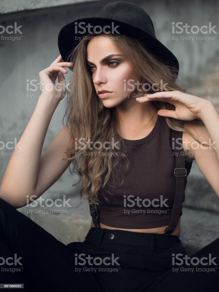 A pretty girl in a stylish black hat and short top. Fashion portrait of Caucasian white girl. stock photo