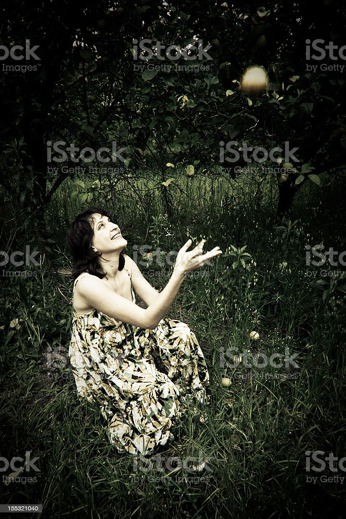 Pretty girl in field catching lemon falling from tree royalty-free stock photo