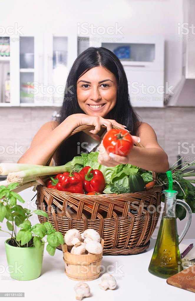 Pretty girl in her kitchen with  vegetable ingredients stock photo
