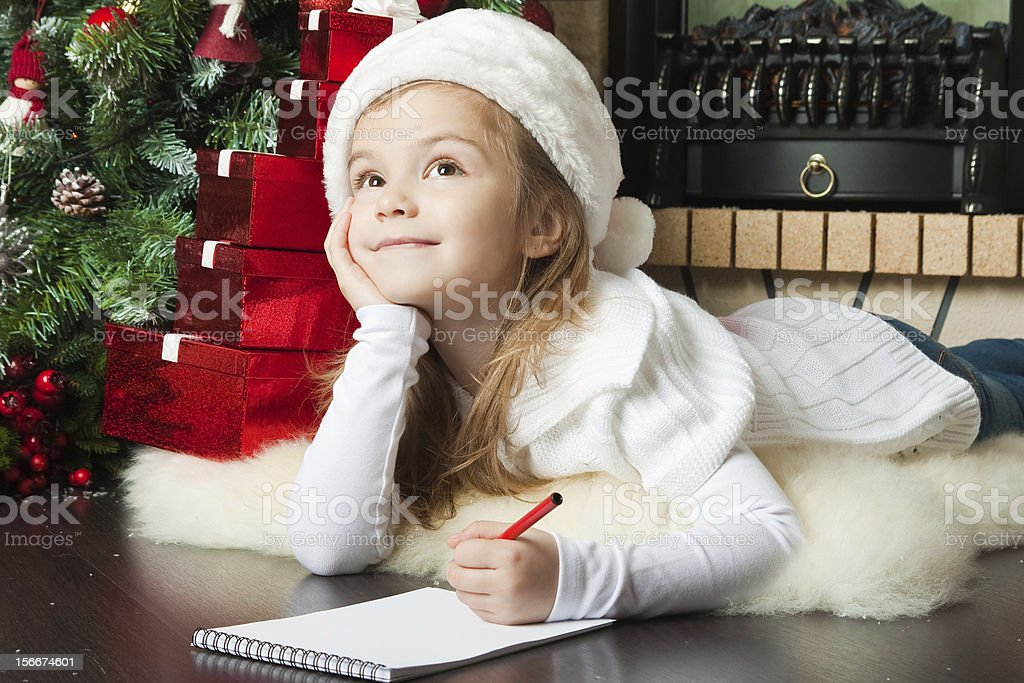 Pretty girl in Santa hat writes letter stock photo