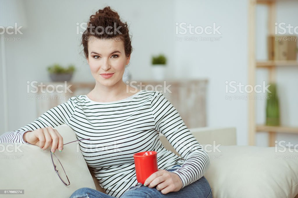 Pretty girl is enjoying hot drink stock photo