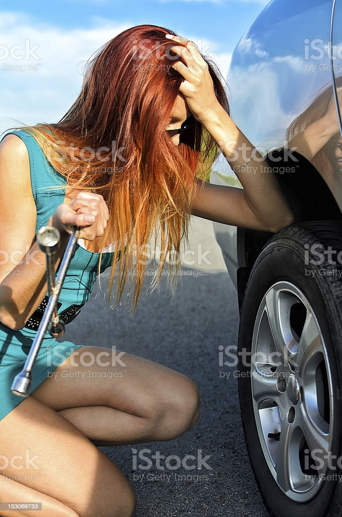 Pretty girl is trying to change a tire royalty-free stock photo