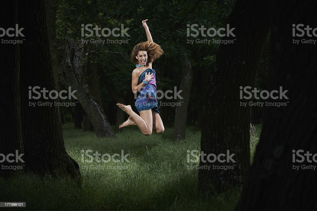 Pretty girl jumping in woods stock photo