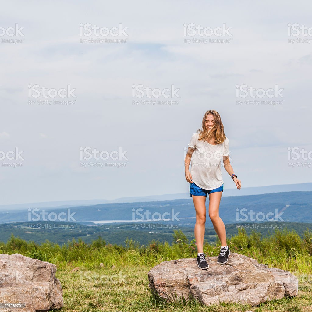 Pretty girl jumping over rocks at the top of mountain stock photo