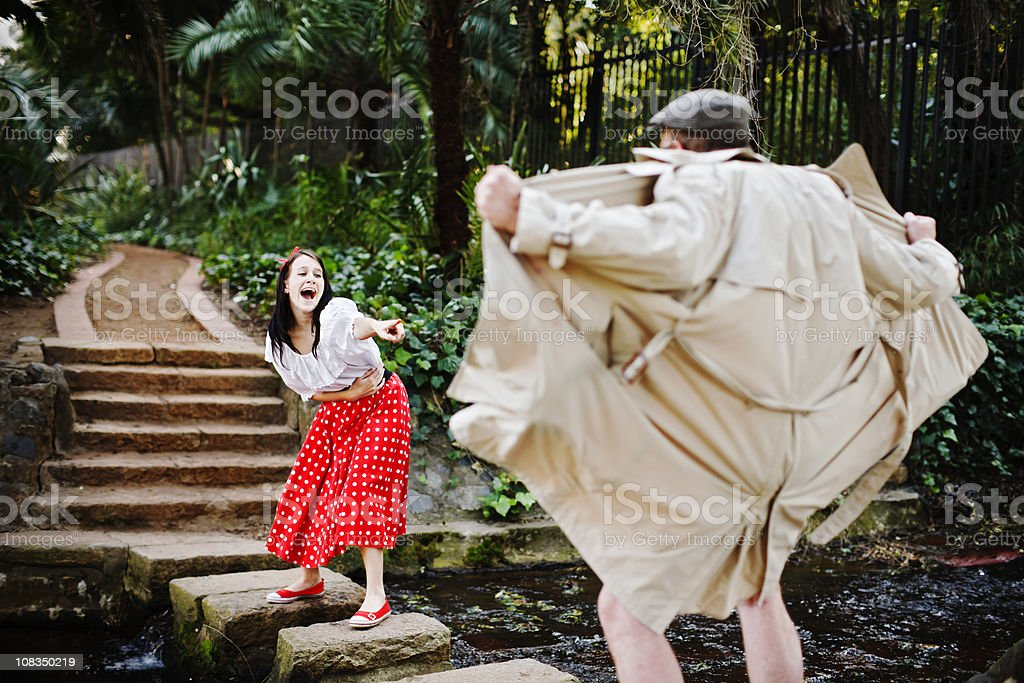 Pretty girl laughs and points mockingly at flasher in park royalty-free stock photo