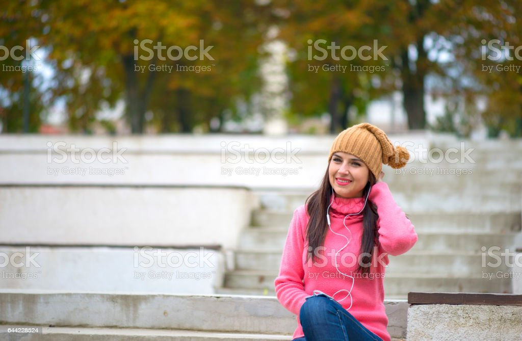 Pretty girl listening music with her headphones in the street stock photo