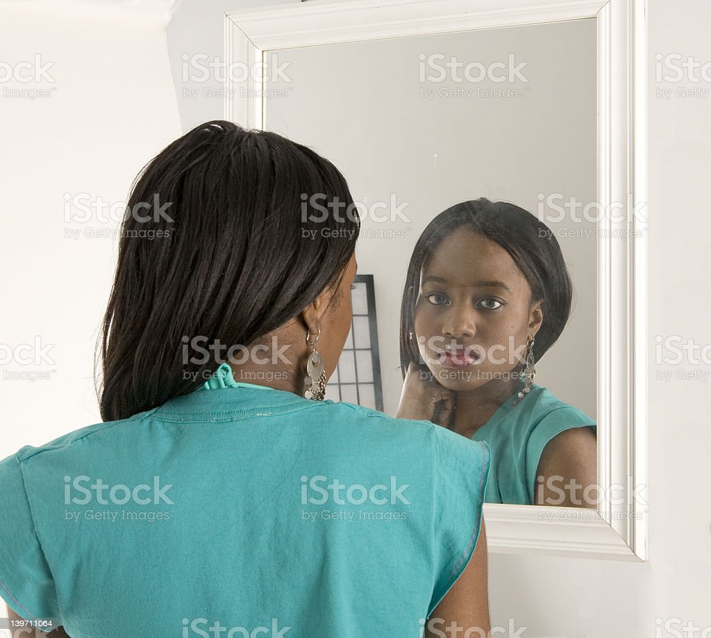 Pretty girl looking in a mirror royalty-free stock photo