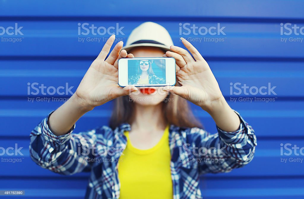 Pretty girl makes self-portrait on the smartphone stock photo