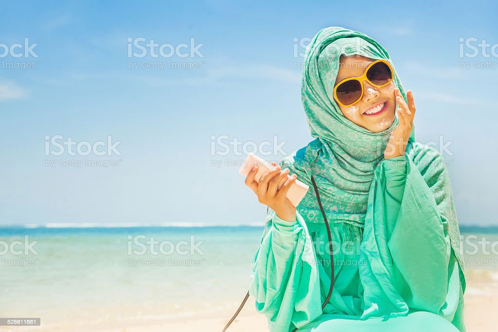 pretty girl on a beach wearing traditional muslim costume stock photo
