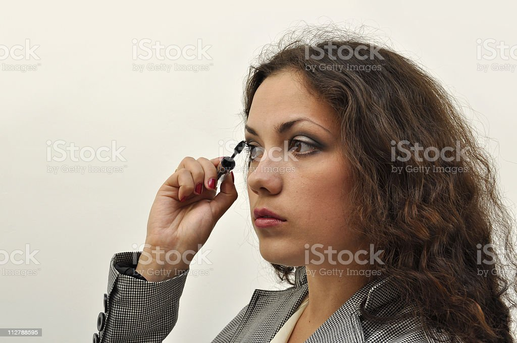 Pretty girl painting her lashes stock photo