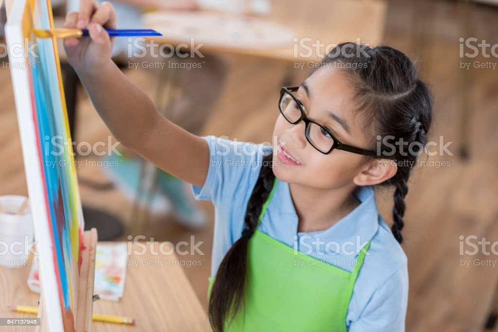 Pretty girl paints in art class stock photo