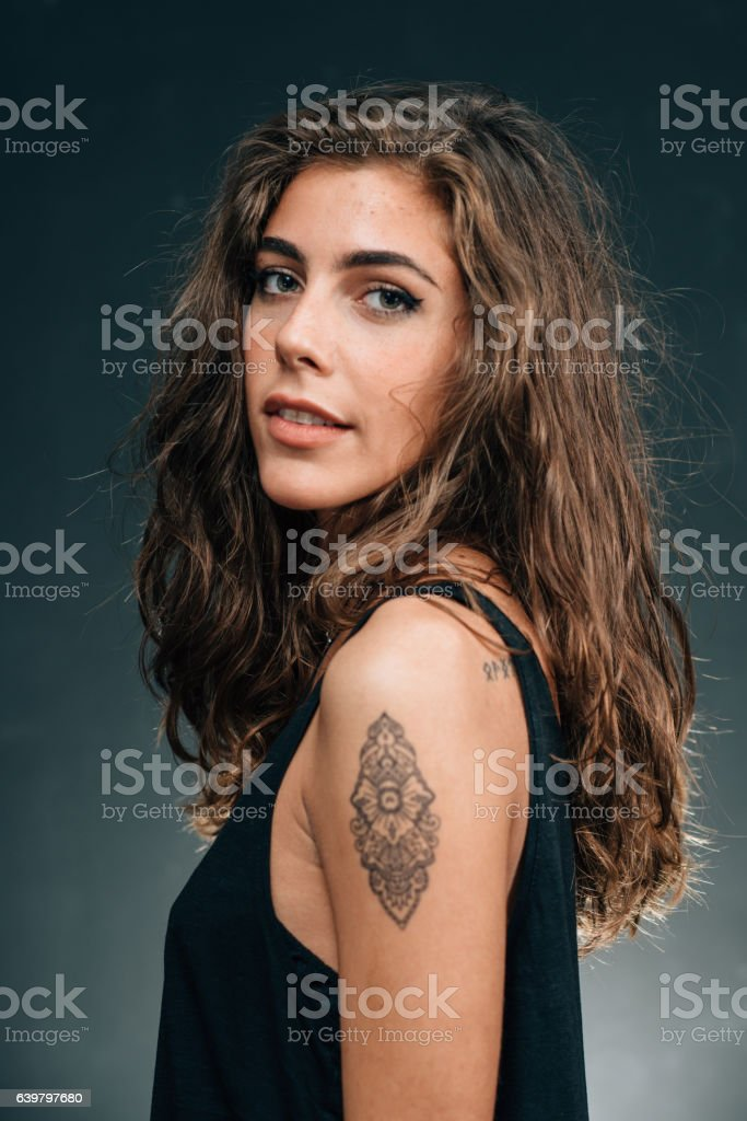 Pretty girl posing with her new tattoo stock photo