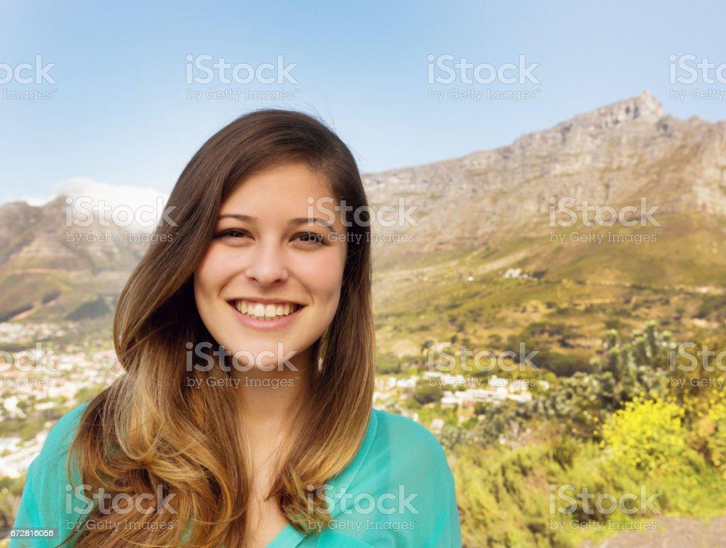 Pretty girl posing with Table Mountain backdrop smiles stock photo