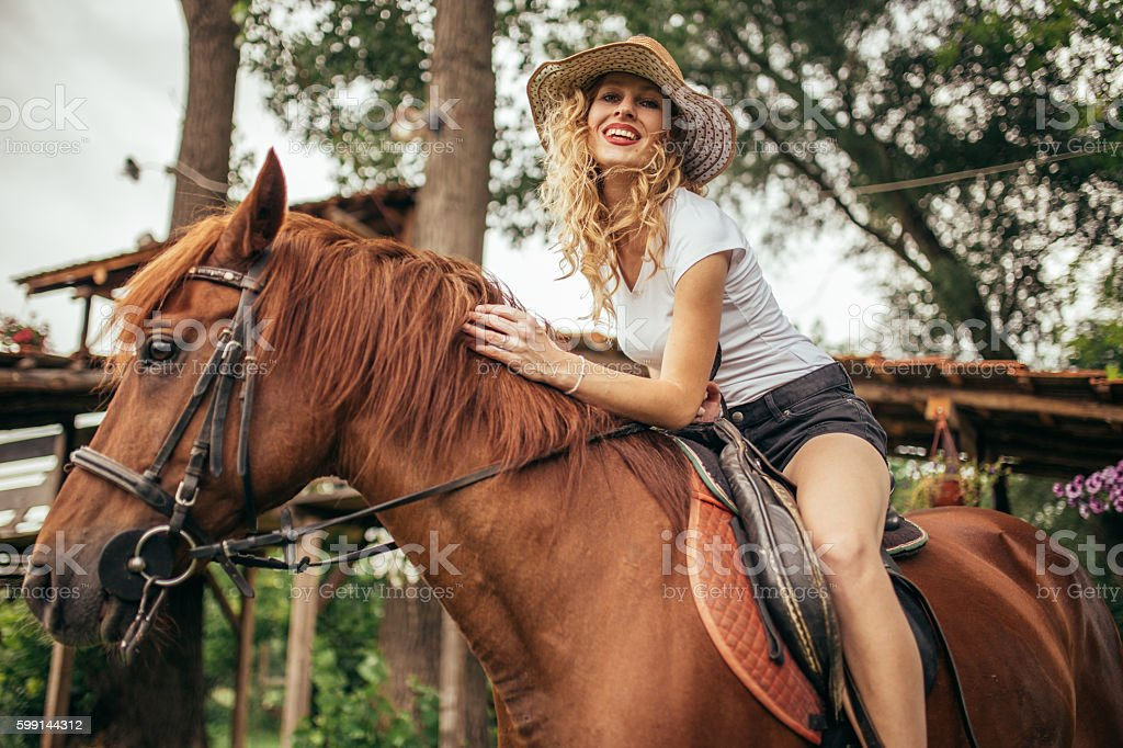 Pretty girl ridding a horse stock photo
