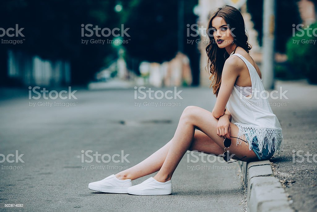 pretty girl sitting in a city street stock photo