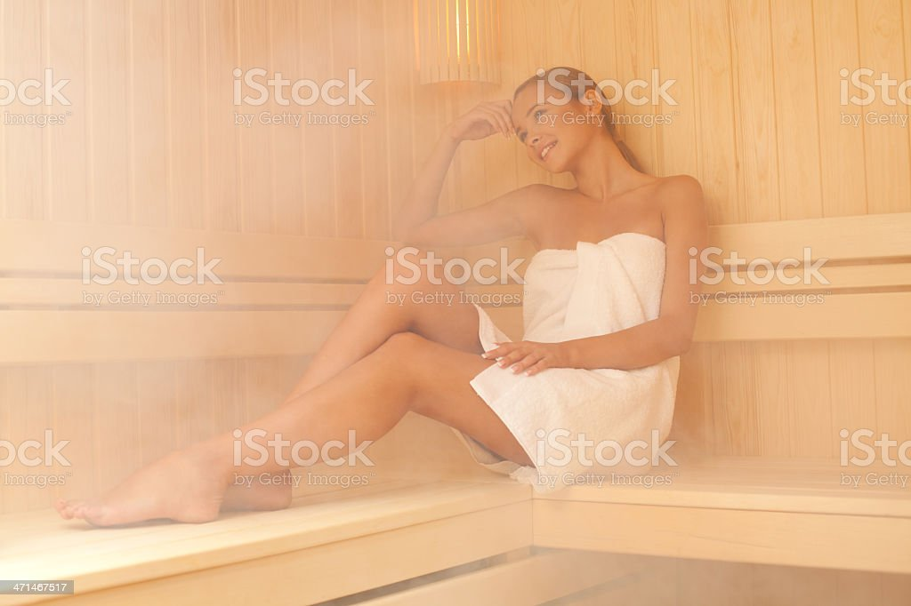Pretty girl sitting in a sauna stock photo