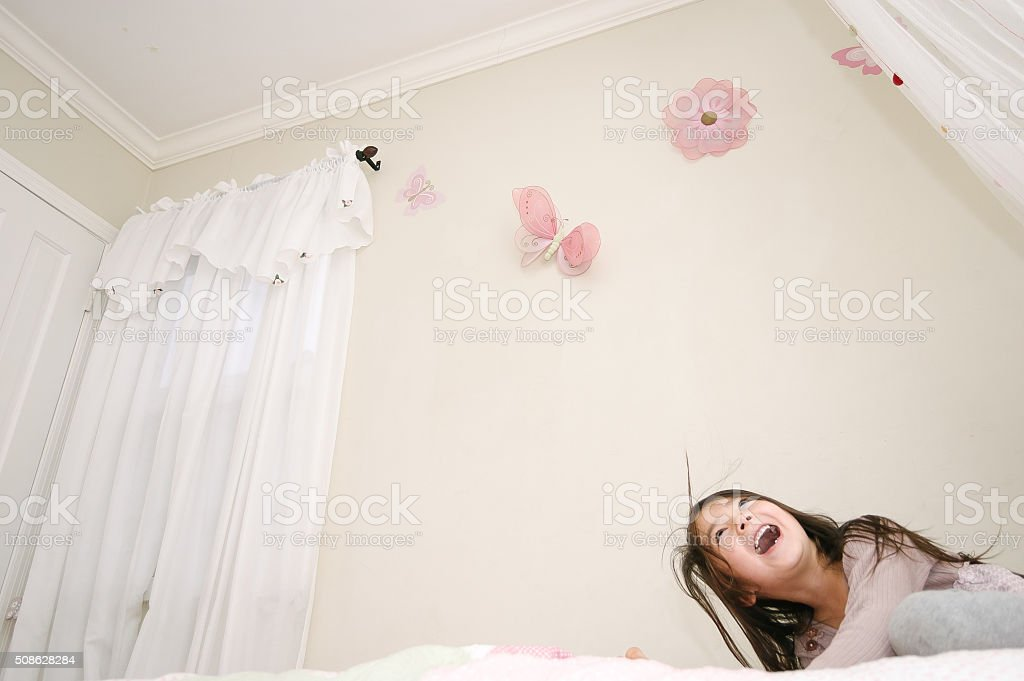 Pretty girl sitting on her bed laughing stock photo
