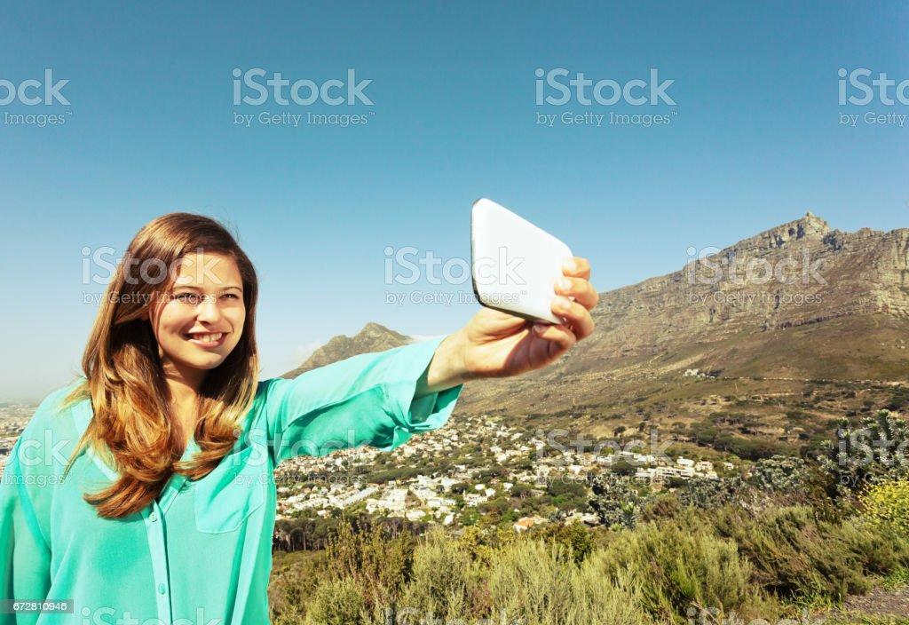 Pretty girl taking selfie with Table Mountain backdrop smiles stock photo