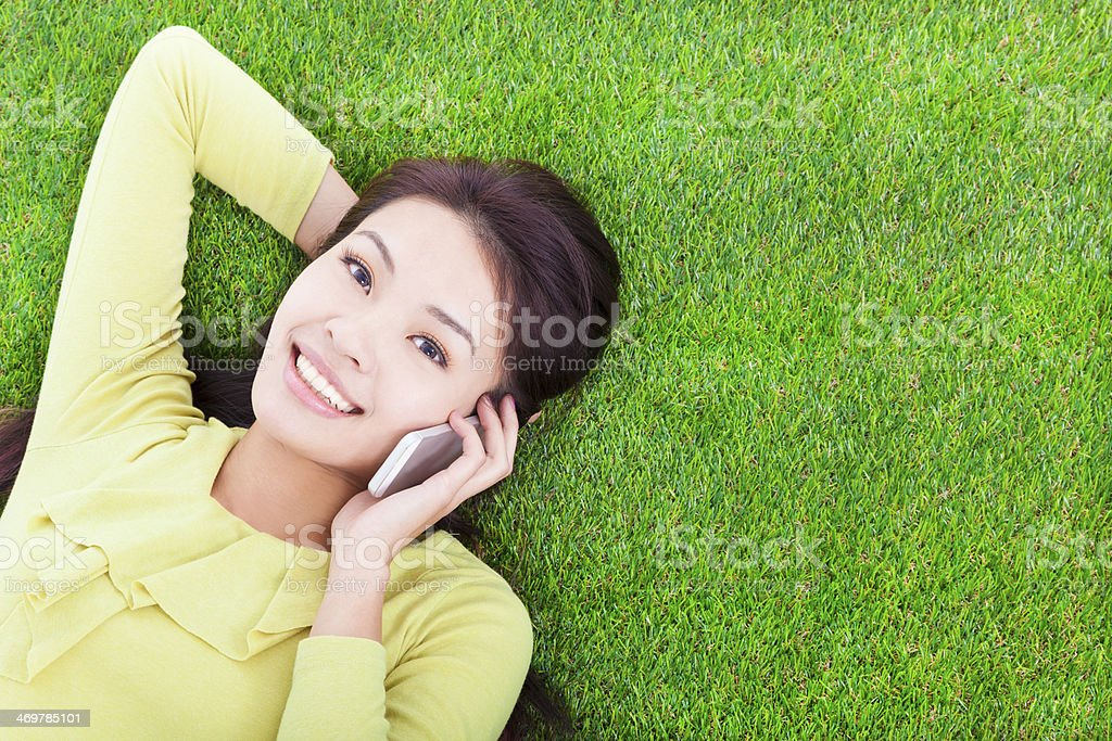 pretty girl talking over the phone in a meadow stock photo