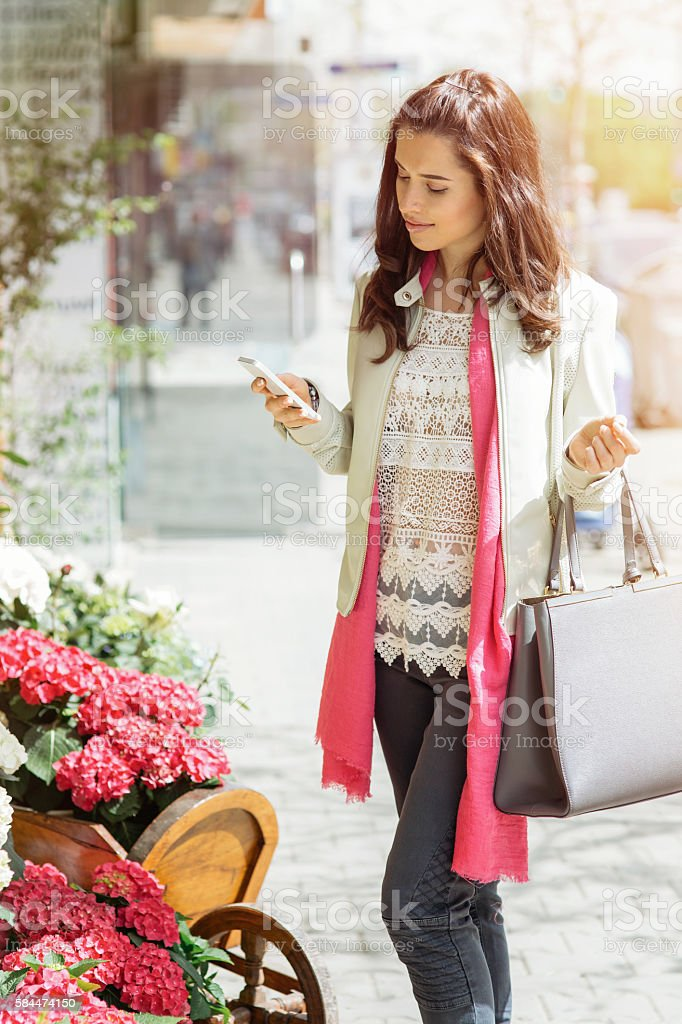Pretty girl texting on cell phone stock photo