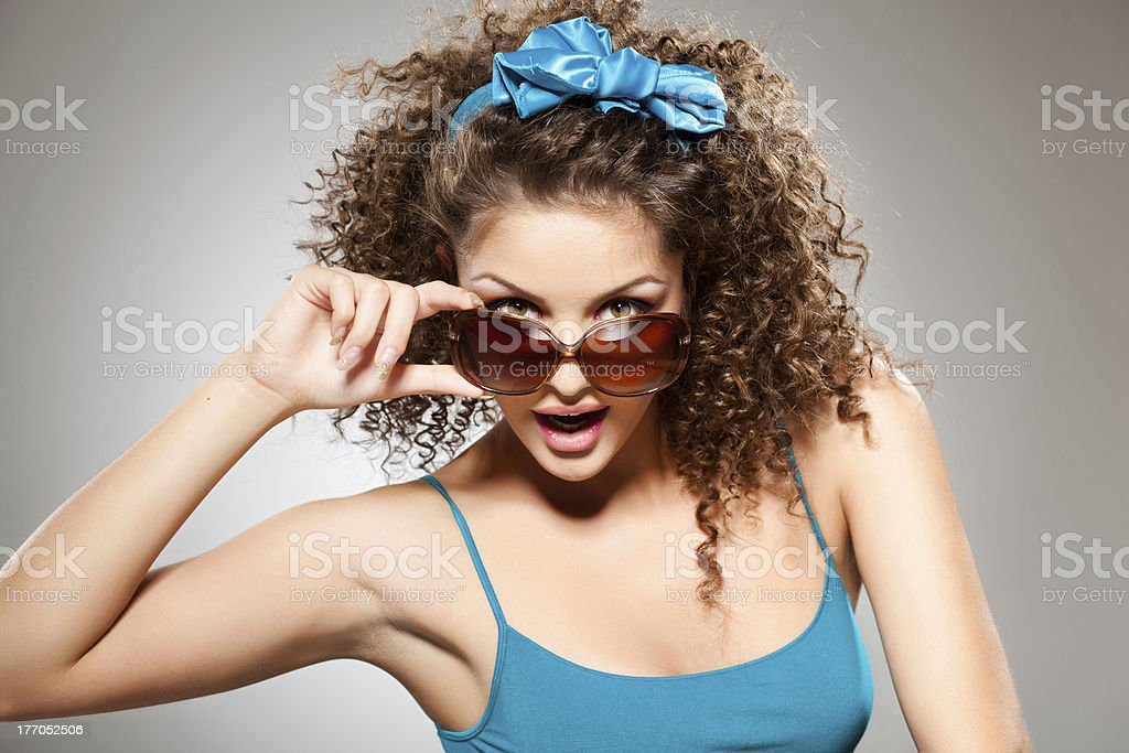 pretty girl with curly hair wearing sunglasses royalty-free stock photo