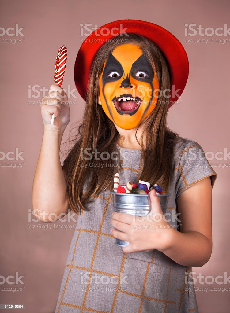 Pretty girl with face painting of a pumpkin stock photo