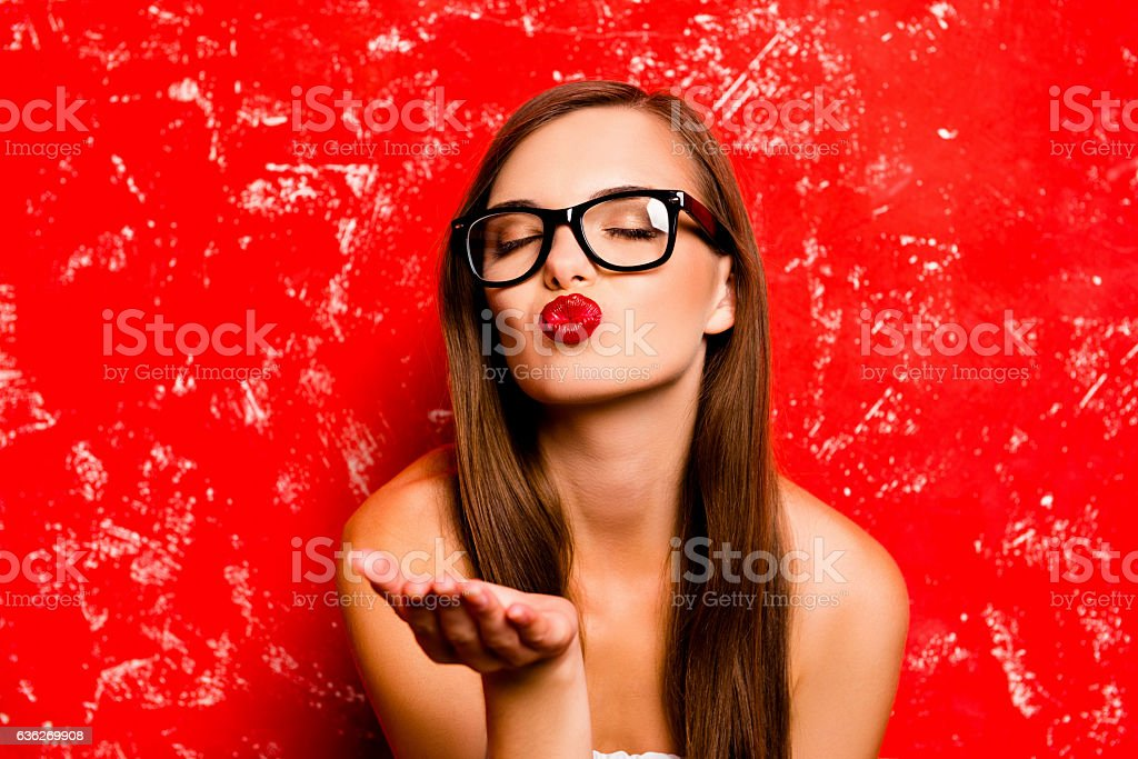 Pretty girl with glasses sending a kiss near red background stock photo
