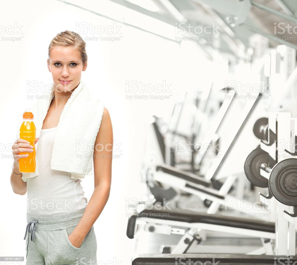 Pretty girl with sports drink next to gym equipment royalty-free stock photo