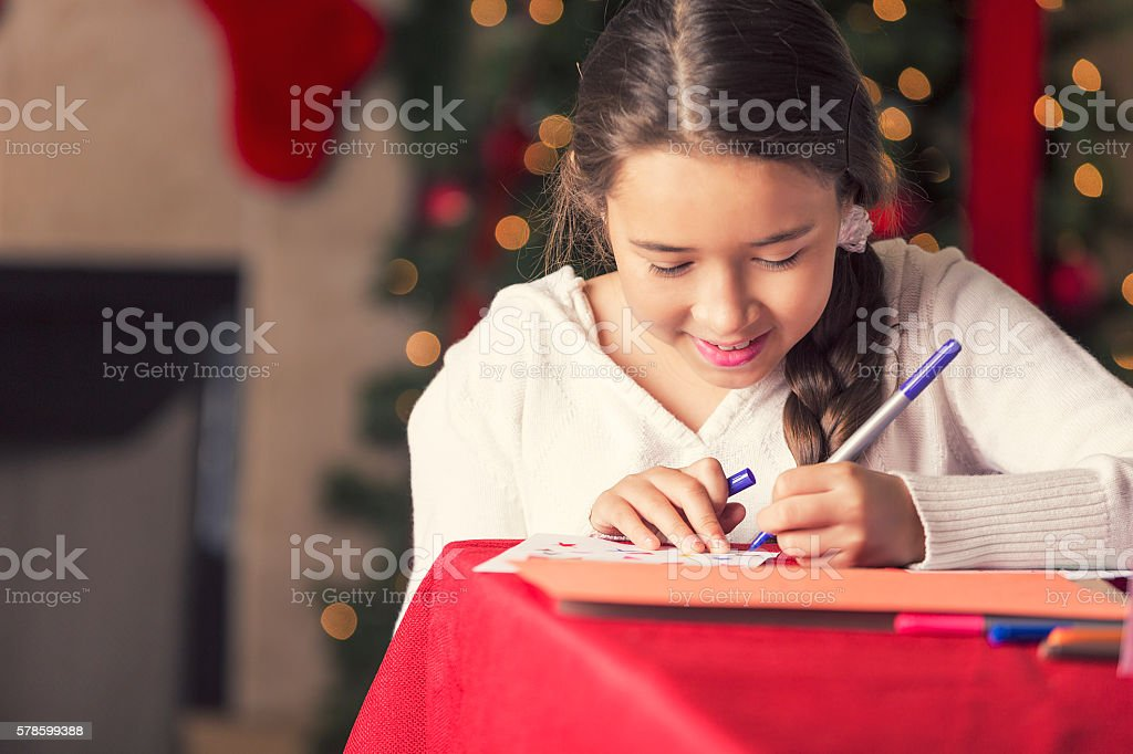 Pretty girl writing in a Christmas card to Santa stock photo