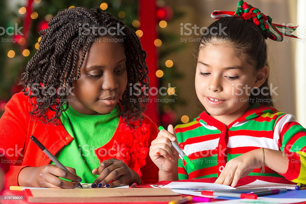 Pretty girls making Christmas cards together stock photo