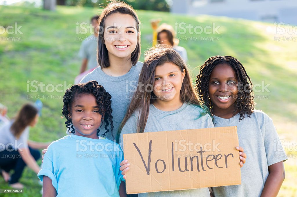Pretty group of young girl volunteers holding sign stock photo