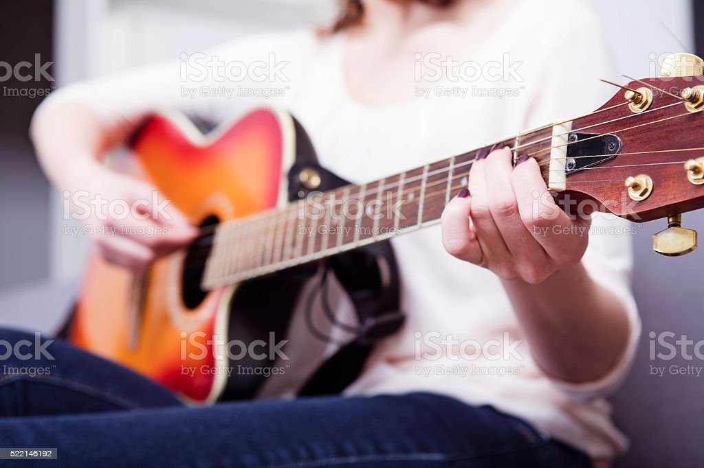 Pretty handsome woman playling some records on guitar , close up stock photo