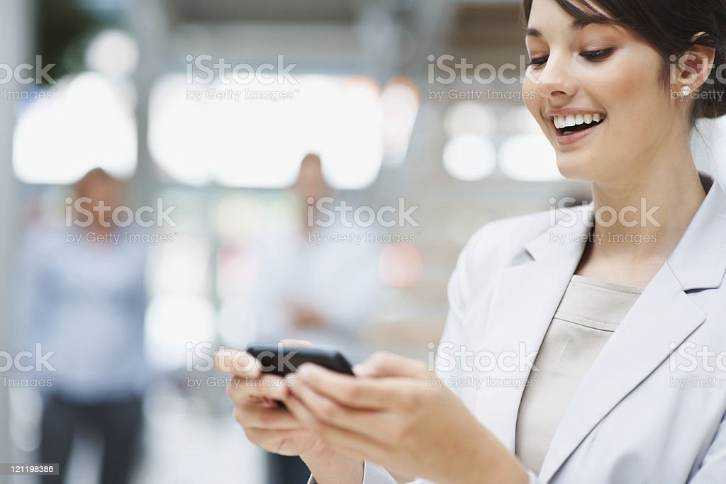 Pretty happy executive reading SMS - blurry background royalty-free stock photo