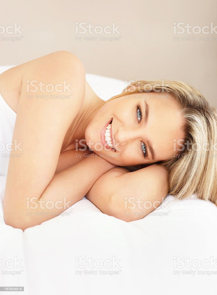 Pretty happy young girl smiling on bed royalty-free stock photo