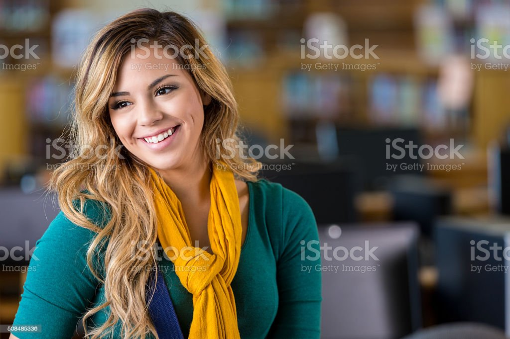 Pretty high school or college student in library stock photo