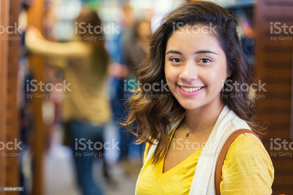 Pretty high school or college student stands in school library stock photo