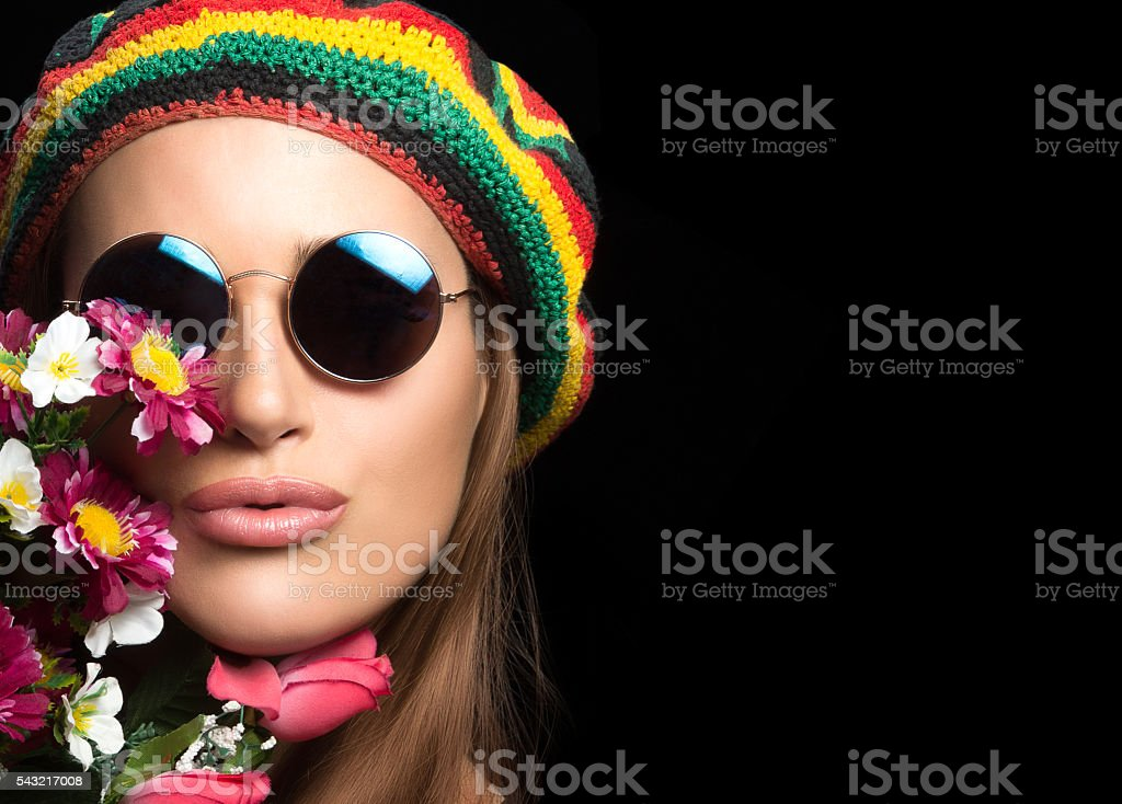 Pretty hippie girl in round sunglasses with flowers stock photo