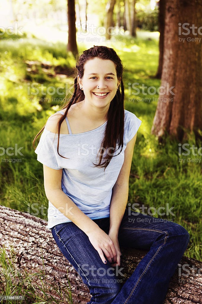 Pretty hippie in jeans and dreadlocks sits on log smiling royalty-free stock photo