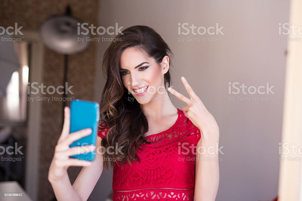 Pretty hipster girl taking selfie and making duck face. Sending stock photo