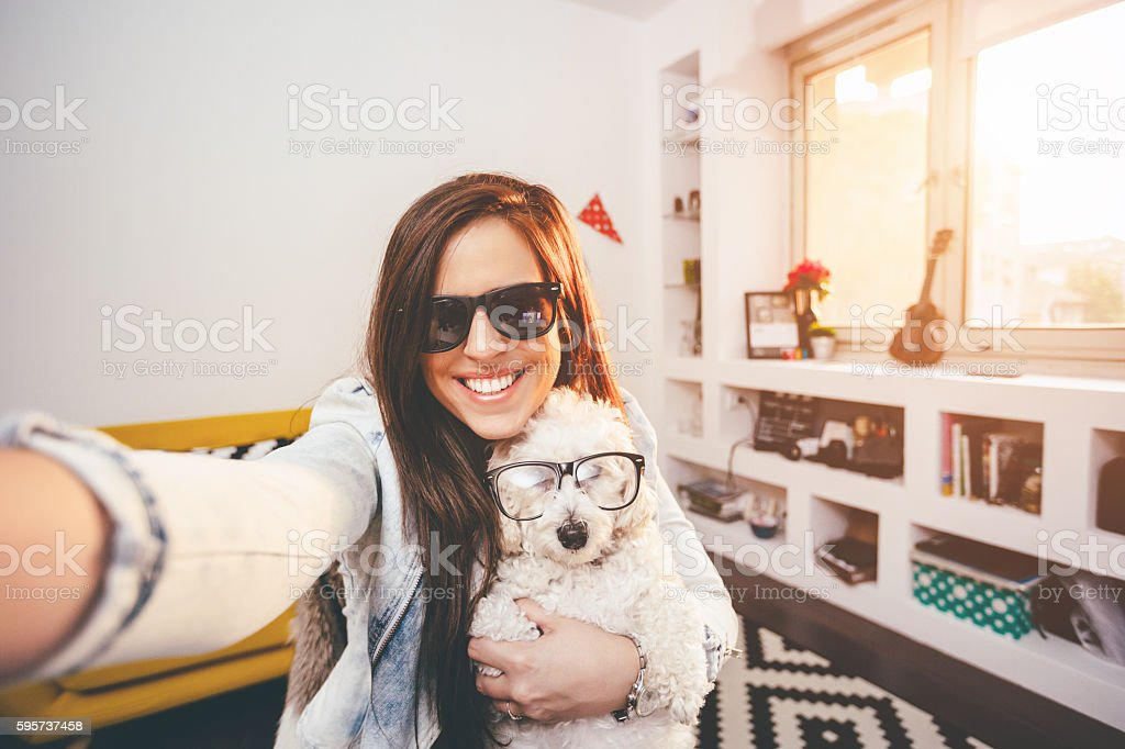 Pretty hipster girl taking selfie with her funny dog stock photo