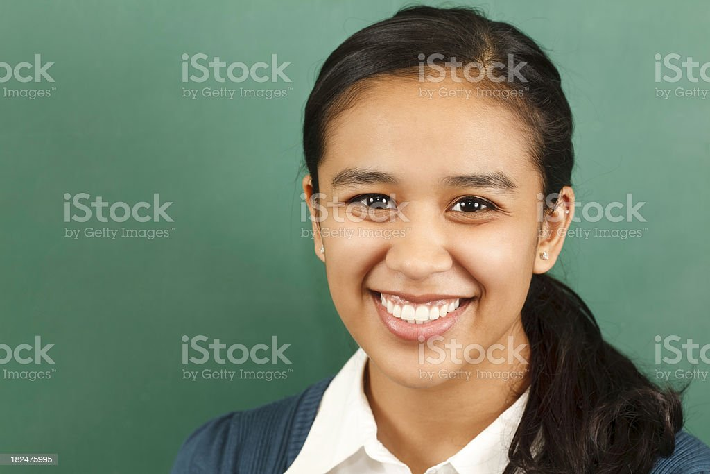Pretty Hispanic College Student in front of School Chalkboard royalty-free stock photo