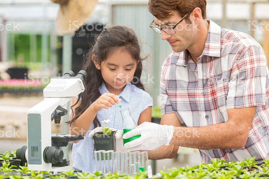 Pretty Hispanic elemntary school student and science teacher stock photo