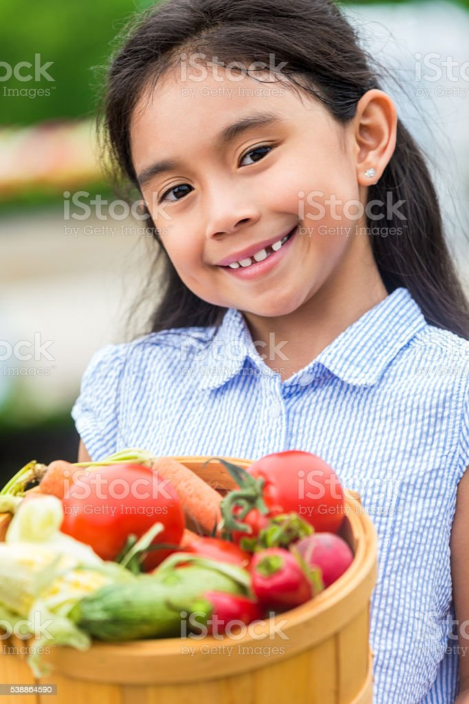 Pretty Hispanic Girl holding fresh vegetables stock photo