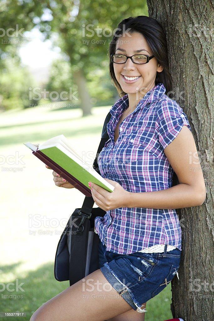 Pretty hispanic girl reading royalty-free stock photo