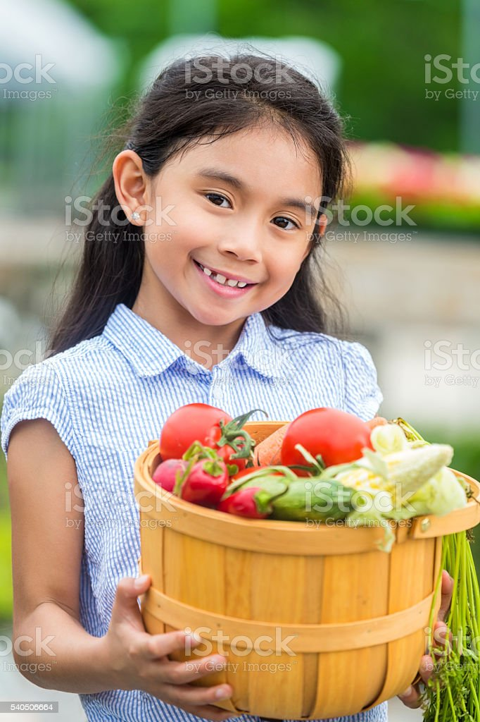 Pretty Hispanic girl with fresh vegetables stock photo