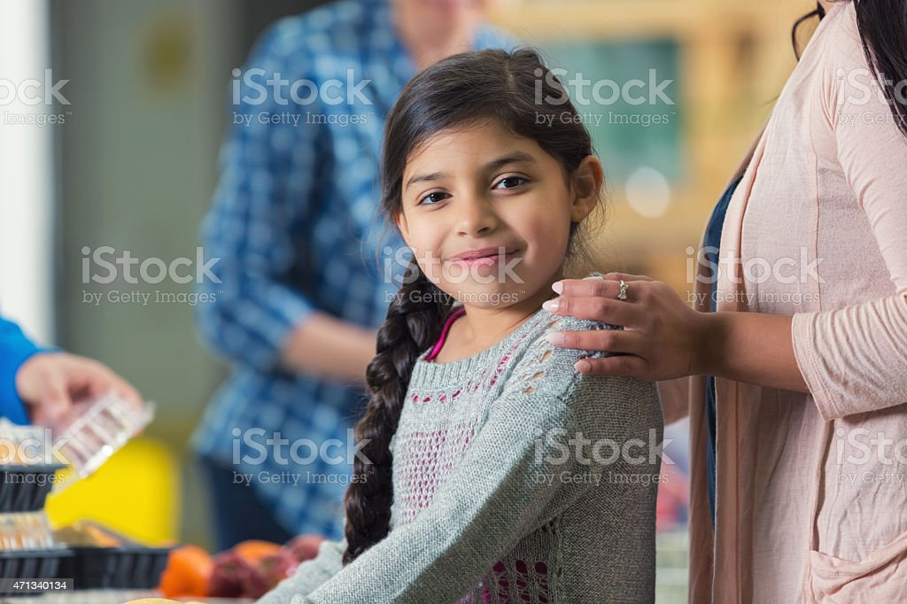 Pretty Hispanic little girl in line at food bank kitchen stock photo