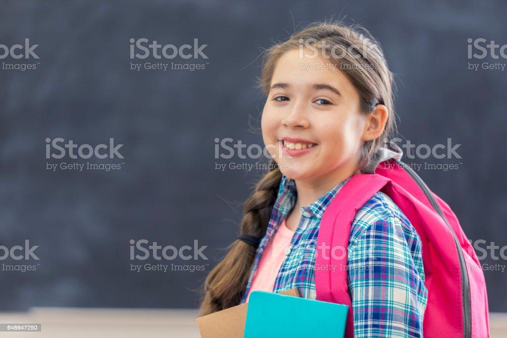 Pretty Hispanic schoolgirl in class stock photo
